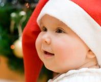 Little smiling girl in red Santa hat Stock Image