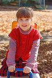 Little smiling girl sits on wooden seesaw Stock Photos