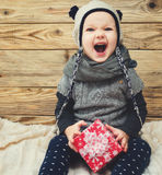 Little smiling girl sitting with gift. Royalty Free Stock Photography