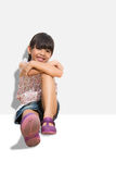 Little smiling girl sitting on the ground Royalty Free Stock Photography