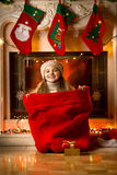 Little smiling girl sitting in red bag for gifts at fireplace Stock Image
