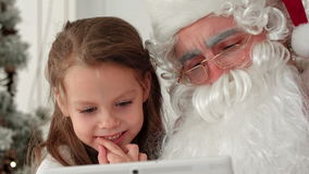 Little smiling girl sitting with Santa using tablet stock video