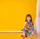 Little smiling girl sitting on swings indoors Stock Photo