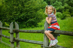 Little smiling girl sitting on wooden fence Stock Photos