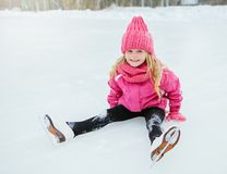 Little smiling girl skate and fell on ice in pink wear. Outdoor. Stock Photo