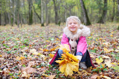 Little smiling girl squats with maple leaflets Royalty Free Stock Image