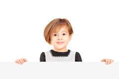 Little smiling girl standing behind a blank panel Royalty Free Stock Photos