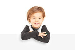 Little smiling girl standing behind a blank panel Royalty Free Stock Images