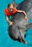 Little Smiling Girl Swimming with the Dolphin. In the Swimming Pool in the Bright Sunny Day Royalty Free Stock Photos
