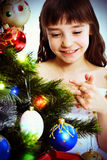 Little smiling girl under a Christmas tree. Looking at Christmas-tree decoration Royalty Free Stock Photo