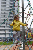 A little smiling girl using the sports equipment in a playground of an apartment house`s court yard stock photo
