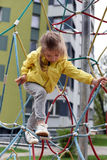 A little smiling girl using the sports equipment in a playground of an apartment house`s court yard royalty free stock photos