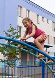 A little smiling girl using the sports equipment in a playground of an apartment house& x27;s court yard stock photo