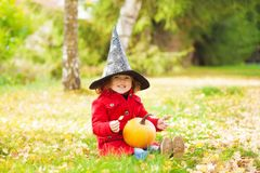 Little girl wearing Halloween witch hat and warm red coat, having fun in the park, autumn day. Stock Photography