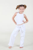 Little smiling girl in white clothes stands and poses. Royalty Free Stock Image