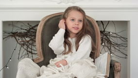 Little smiling girl in white sweater sitting on a chair wrapped in white Christmas blanket stock video