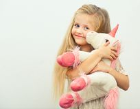 Little smiling girl with white unicorn toy. Isolated portrait of girl with long blond hair Royalty Free Stock Images