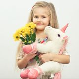 Little smiling girl with white unicorn toy. Yellow flowers.  portrait of girl with long blond hair Royalty Free Stock Photo