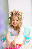 Little smiling girl with wreath and books. Little smiling girl with curly hair covered with wreath and books indoors Stock Photos