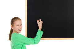 Little Smiling Girl Writing On A Blackboard. Smiling girl in green blouse holding white chalk writing on a blackboard and looking at camera. Waist up studio shot Royalty Free Stock Photos