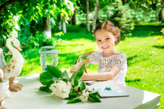 Little smiling girl  writing on notebook outdoor in the park. Vi Royalty Free Stock Images