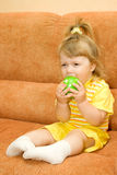 Little smiling girl in yellow eat apple Stock Images