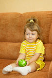 Little smiling girl in yellow eat apple Royalty Free Stock Photo