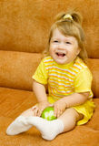 Little smiling girl in yellow eat apple Royalty Free Stock Photography