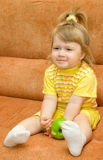 Little smiling girl in yellow eat apple Stock Photos