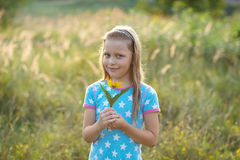 Little smiling girl with yellow flower Stock Photo