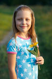 Little smiling girl with yellow flower Stock Image