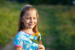 Little smiling girl with yellow flower Royalty Free Stock Photo