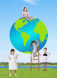 Little smiling girls with a globe Stock Images