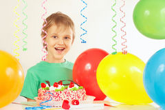 Little smiling kid with birthday cake and balloons Royalty Free Stock Images