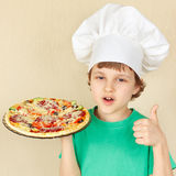 Little smiling kid in chefs hat with cooked appetizing pizza Royalty Free Stock Images