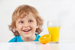 Little smiling kid with a glass of fresh juice and orange Stock Photography