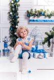 Little smiling pretty girl sitting next to a Christmas tree Royalty Free Stock Images