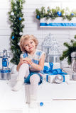 Little smiling pretty girl sitting next to a Christmas tree Stock Photos