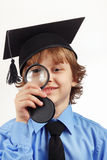 Little smiling professor in academic hat with a magnifying glass on white background Royalty Free Stock Images