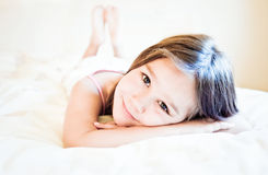 Little smiling relaxing girl. Studio portrait of a cute little Caucasian girl child smiling while relaxing Stock Image