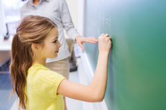 Little smiling schoolgirl writing on chalk board Royalty Free Stock Photography