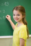 Little smiling schoolgirl writing on chalk board Royalty Free Stock Photo