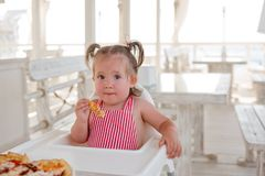 A little smiling toddler girl is sitting at a table in a summer cafe in the seaside resort. stock photos