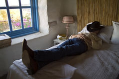 Little Snooze. A man laying on a bed with a cowboy hat over his eyes taking a little time out rest Royalty Free Stock Photography