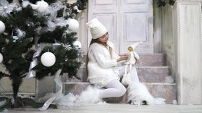 Little snow elf sitting under the tree with a doll on the steps near the door stock footage