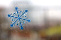 A little snow-flake. A little snow flake on the glass of window in the winter cold day.  Different shape of flakes made them unique Stock Photo