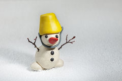 Little snowman made of plasticine standing on real snow Royalty Free Stock Images