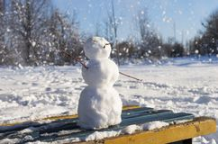 A little snowman standing on the bench in the park. While it is snowing on sunny winter day royalty free stock image