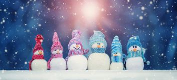 Little snowmans on soft snow on blue background stock image