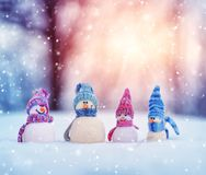 Little snowmans on soft snow on blue background royalty free stock photo